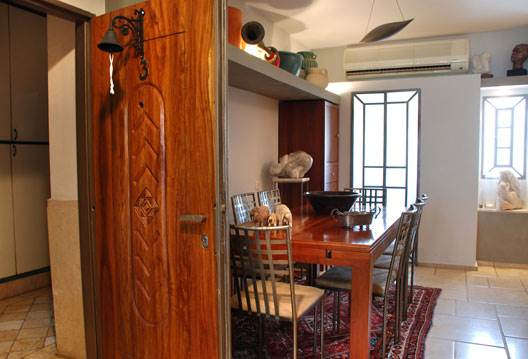 לוח עץ שגולף והודבק על דלת הכניסה לבית<br/>(צילום: לירז פאנק)