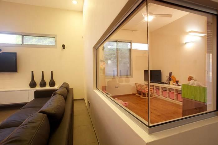חלון הצצה בסלון פונה לחדר המשפחה ומאפשר שקט, סדר ופרטיות לשני הצדדים. (צילום: דרור כץ)