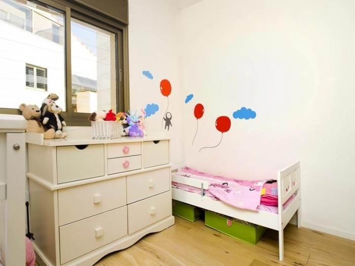 חדר הילדים עוצב בקווים מינימליסטיים אך חמים, בשילוב מדבקת קיר ופרקט ליצירת מראה ביתי ונעים (צילום: טכנוגרפיקס, יניב שוורץ)