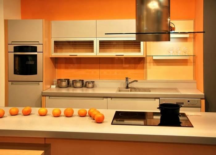מטבח לבן או אפור בו אחד הקירות צבוע בכתום עז של נירלט, יתן מראה מעוצב ושיקי (צילום: דן לב)