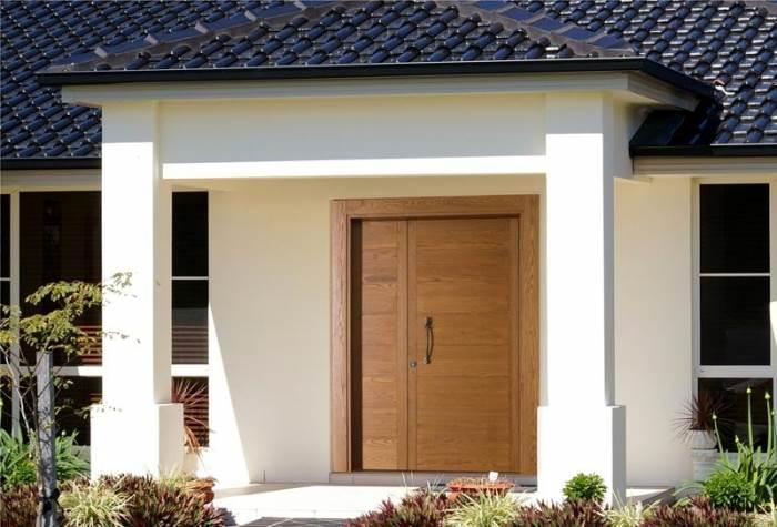 דלת כניסה לבית של open gallery העשויה מעץ גושני, מקרבת אותנו לטבע ומייצרת תחושת חמימות ביתית (צילום: יח