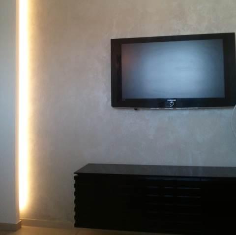 גבס צורני ועדין, תאורת לד סמויה, גמר דקורטיבי לקיר עם ארון מרחף שחור - ממוקמים דווקא בחדר המיטות (צילום: שי אפשטיין)