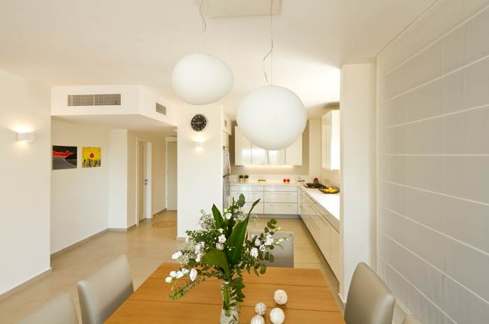 את התפאורה הביתית משלים וילון בצבע בהיר וזוג גופי תאורה ביצתיים. מבט נוסף לפינת האוכל