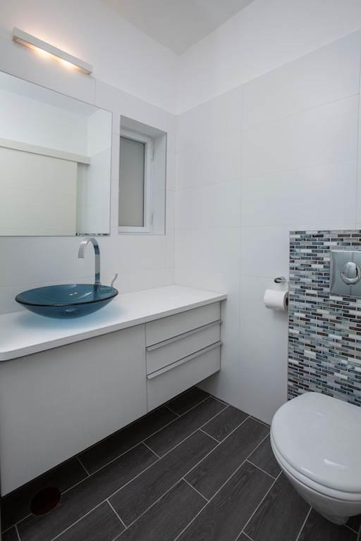 הפסיפס משמש כחולייה מקשרת לאלמנט הלבנים, שחוזר על עצמו גם בשאר חלקי הדירה. חדר האמבטיה. גוף תאורה: Thomas עיצוב ותכנון תאורה.