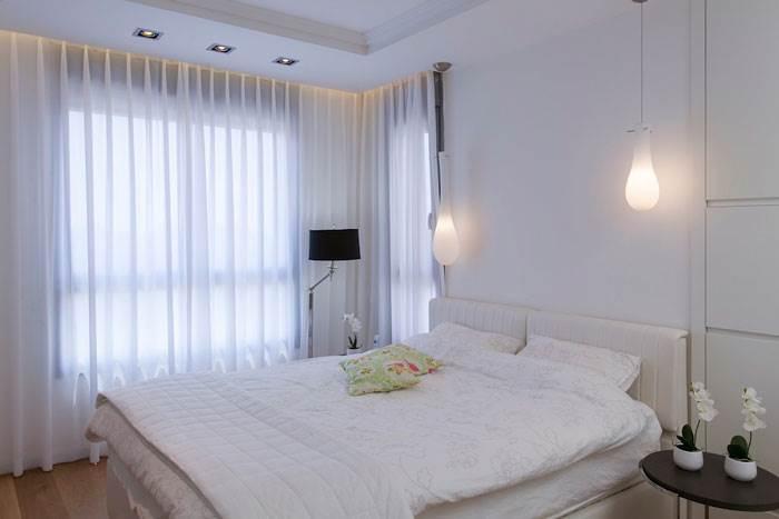 חדר שינה עוצב בסגנון קלאסי עם גופי תאורה דמויי טיפות מעל המיטה