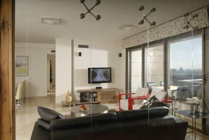 מבט מחדר העבודה - קיר הזכוכית מאפשר פרטיות במשרד, אך גם אפשרות להצצה לסלון. מזנון, כורסאות ושולחן סלון בעיצוב יפרח בן צבי.