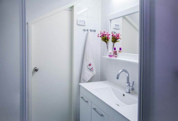 הקירות חופו בלבן ליצירת מרחב: חדר רחצה נעים ונוח. דלת בהזמנה אישית מהנגר: עמי אוחנונה
