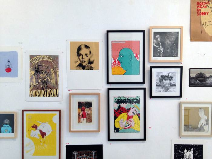 קיר עם הדפסים של אמנים, מעצבים ומאיירים איתם הגלריה משתפת פעולה. מתוך תערוכת המכירה השנתית
