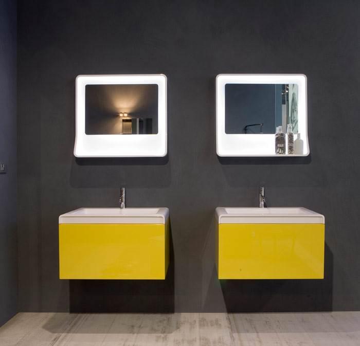 צהוב גם באמבטיה. יחידות כיור בצהוב של חברת ANTONIOLUPI על רקע קיר שחור, שמבליט את הצבע ונותן לו כח בחלל. להשיג בחזי בנק.