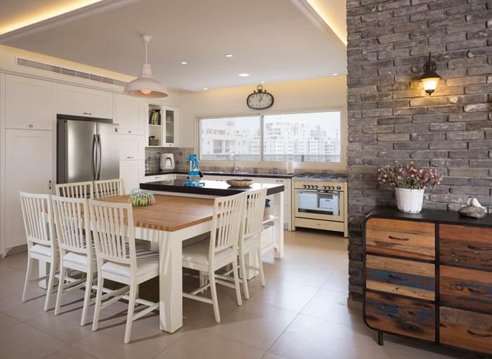 פתרון חלופי לפינת האוכל נמצא בחלל המטבח עם שולחן עץ קל להזזה