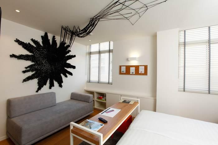 טל שושן, שושןשחור, פנימיות אופניים, בד, 2014. הפרח השחור המתפשט כמו צמח מטפס על גבי קיר החדר עשוי כולו מפנימיות של אופניים.