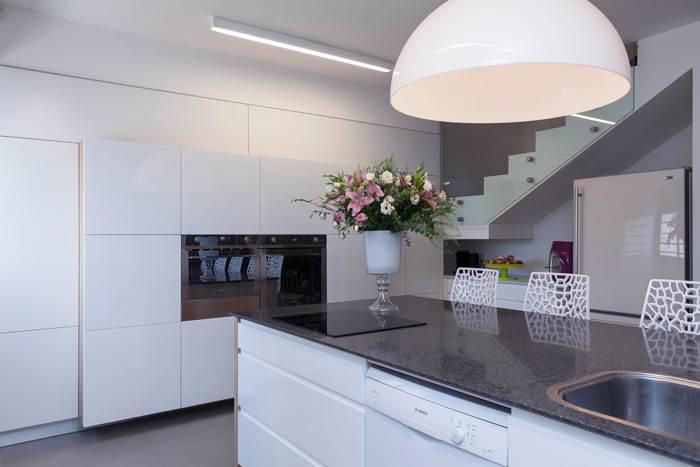 במטבח הוצב אי ארוך המשמש גם לאכילה וגם כמשטח עבודה ותחת מדרגות הבית נוצל החלל למטרות אחסון