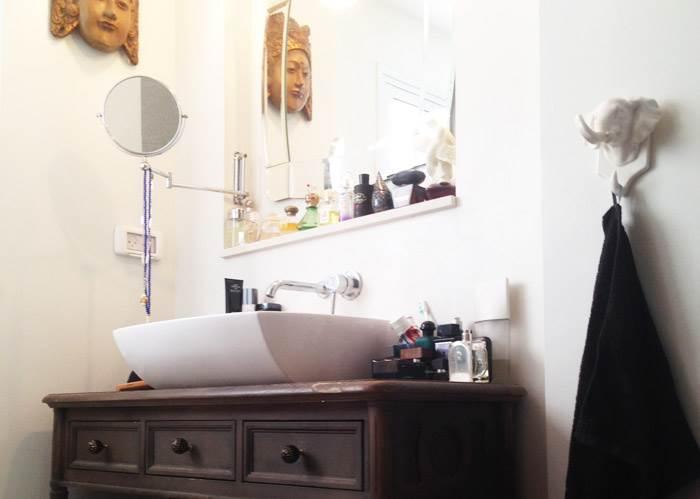 בחדר הרחצה יש שימוש בצבעים נייטרליים ובאריחים לבנים, כדי לייצר תחושת ניקיון. הריצוף באמבטיה הוא גרניט פורצלן במראה בטון, כשעליו שטיח צבעוני, שמוחלף אחת לכמה חודשים. הכיור מונח על שידת מגירות מעץ, שנרכשה כשידת איפור ב KARE DESIGN. המסיכה נרכשה בשוק פשפשים בלונדון.