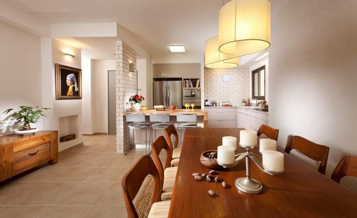 מבט מפינת האוכל לכיוון הכניסה עם קיר בחיפוי לבני סיליקט שהותאם למטבח