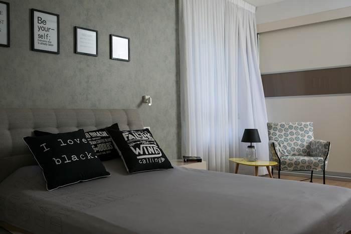 חדר השינה עוצב כסוויטה מפנקת עם טפט אפור ופינת קריאה לרווחת בני הזוג