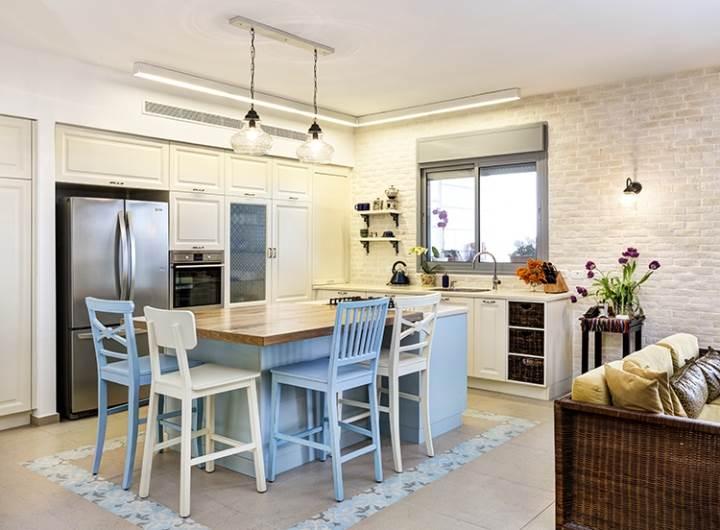 קיר ארונות גבוהים לאחסון ואי עם כיריים: מבט על המטבח