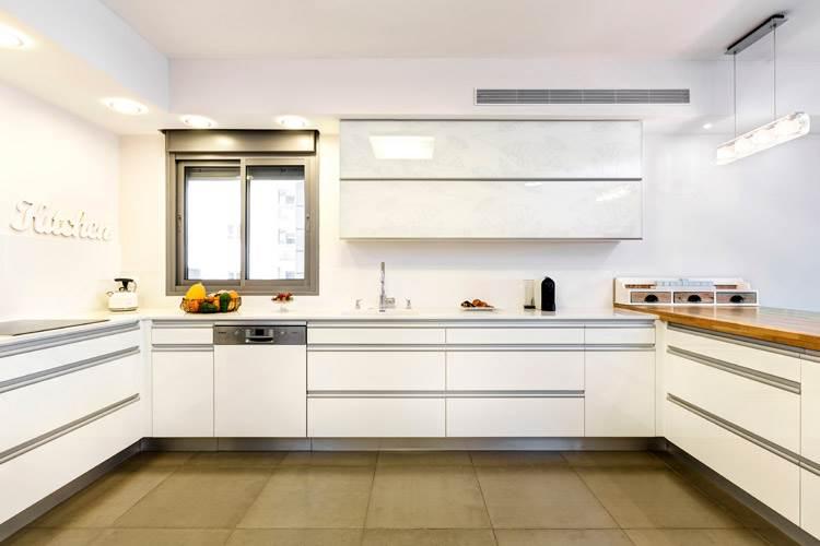 על רקע העיצוב הלבן: ריצוף גרניט פורצלן כהה יותר. מבט על המטבח
