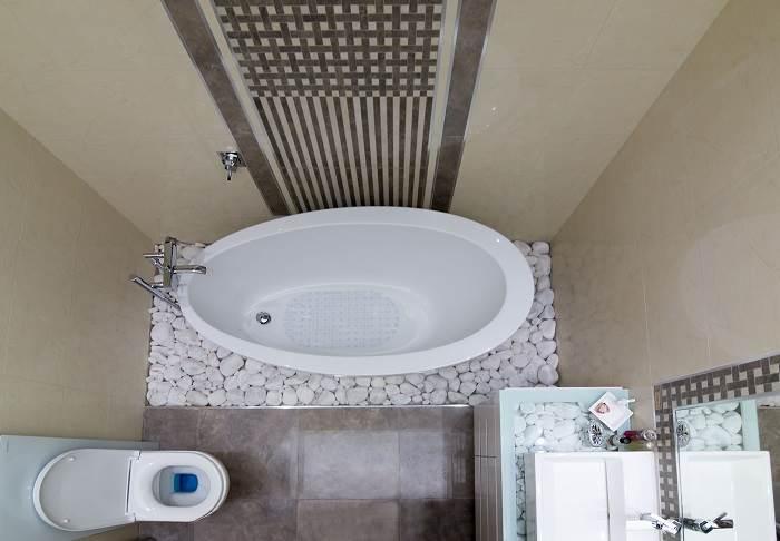 צילום של אמבט רחצה מופרד, מוקף בחלוקי נחל היוצרים תחושה של ספא | צילום: דוד יכין