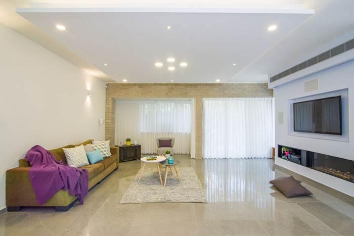 הסלון, כמו כל הקומה, רוצף באריח מבריק כדי לתת לו השתקפות של אור מאחר והוא לא עמוס בפתחים ולא מאוד מואר | עיצוב פנים: אופיר זיו | צילום: עידן גור
