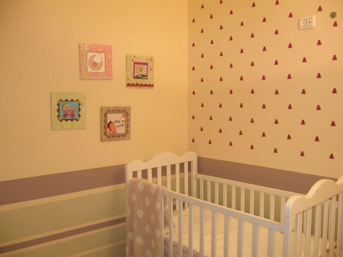 מיטת התינוק לצד הקיר שעוטר בטפט ובפסי הברקוד