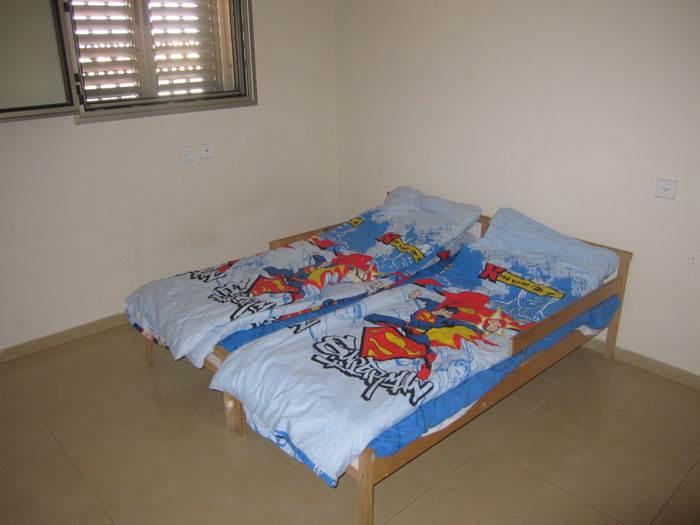 בלי אביזרי טקסטיל, בלי תמונות, רק שתי מיטות במרכז החדר. חדר הילדים לפני השדרוג (צילום: אתר הדירה)