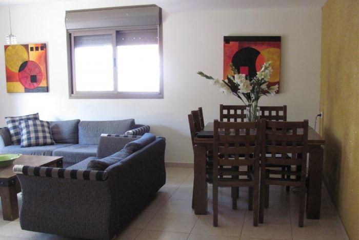 קיר מנצנץ בגוון חרדל, תמונה חסרת שיק ושולחן חסר כל טאצ