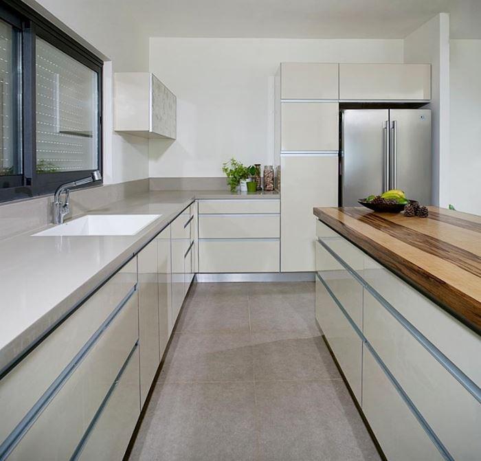 סלע קיומו של המטבח הוא משטח העבודה. מטבח של גאיה מטבחים המשלב משטח מפורמייקה מבריקה ואי עשוי עץ (התמונה באדיבות גאיה מטבחים)