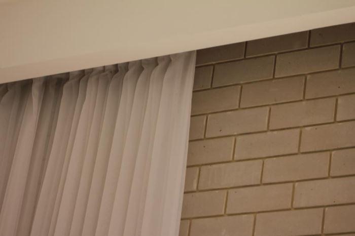 קיר גבס נבנה במיוחד כדי להסתיר את ראש הוילון. קיר של בריקים מקשר בין הסלון והמטבח ובכל החללים משולבים וילונות בעלי מוטיב אחיד שיוצר הרמוניה (צילום: ג