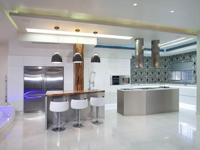 מטבח בעיצובה של איריס שמיר הכולל תאורת לד תחתונה, גופי תאורה צמודי תקרה ונסתרים וכן גופי תאורה תלויים (צילום: יח