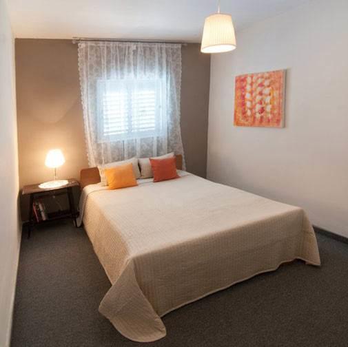 כוחו של טקסטיל. כיסוי המיטה החדש, הוילון, כריות הנוי וגוף התאורה יצרו אווירה נעימה וחמימה יותר בחדר. חדר השינה לאחר השדרוג