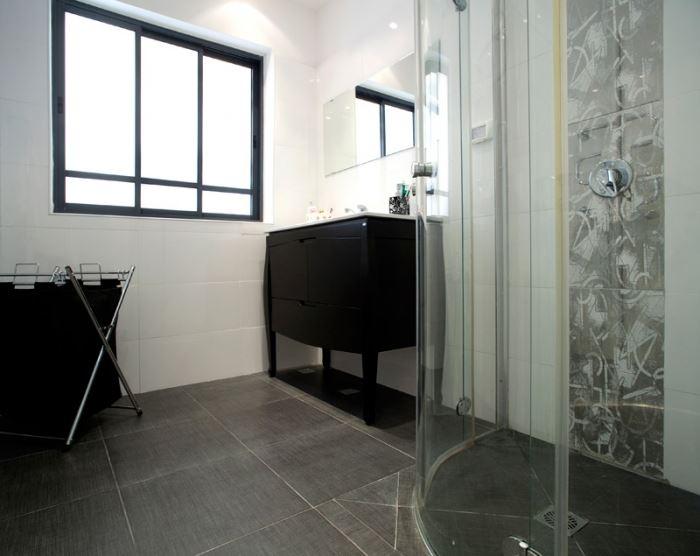 שילוב של גווני אפור ולבן עם פס דקורטיבי לאורך המקלחון המשלב את שני הגווני ומשמש כחוט מקשר ביניהם. חדר האמבטיה לאחר השיפוץ