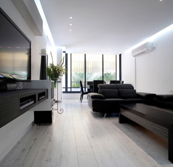 ריהוט בצבע שחור המהווה קונטרסט ללבן הבוק של הפרקט וקירות הבית. הסלון לאחר השיפוץ