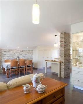 פינת אוכל המשלבת קיר בריקים, עץ וצבעים בהירים. Niego Design
