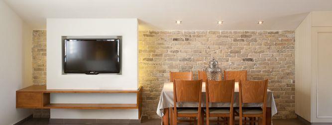 סלון ופינת אוכל הכוללים קיר טלוויזיה בשילוב שידת עץ. Niego Design