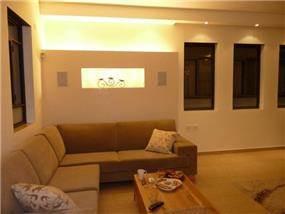 סלון בו מובלטת תאורה אחורית מאחורי הספות, עיצוב סיגל נייגרציק אבירם