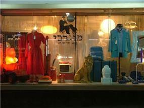 """חלון ראווה של בית קפה וחנות יד שנייה ברחוב אלנבי בת""""א."""