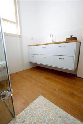 רצפה מעץ בשילוב חלוקי נחל בחדר האמבטיה, עיצוב ניצן הורוביץ