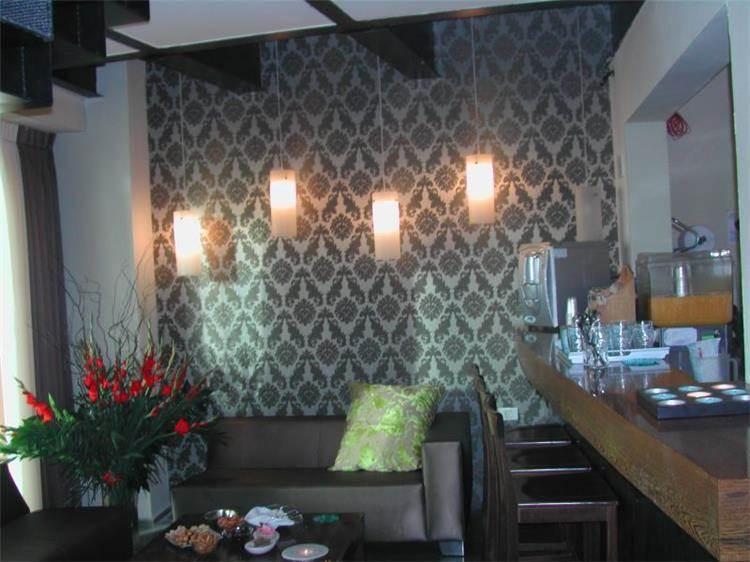 מבואה- חדר ארוח בספא. קיר כפול מחופה בטפט בדוגמת רטרו, ריהוט בגוון מוזהב