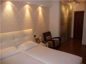 חדר שינה המשלב פרקט כפרי וקיר טפט