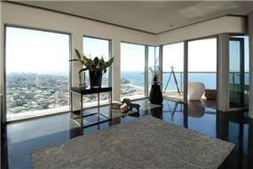 חלל מגורים בתכנון אדריכל נסטור סנדבנק, סלון מוקף חלונות עם נוף לים.