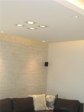 סאלון עם הנמכת גבס וקיר אבן לבנה