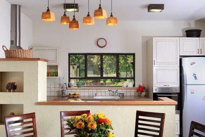 מבט מפינת אוכל למטבח כאשר דלפק משמש חציצה דקורטיבית ופרקטית בין שניהם.