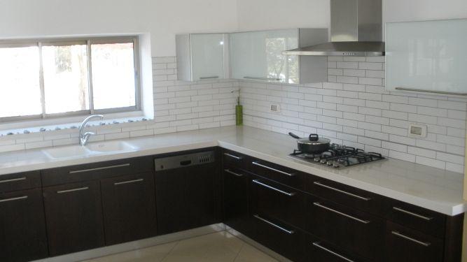 מטבח שילוב עץ וזכוכית, חיפוי קיר לבנים, ארונות מטבח עץ כהה, חיפוי קיר לבן.