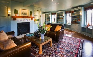 סלון מעוגל, אח במרכז הסלון, שטיחים אתניים, מראה עתיק .