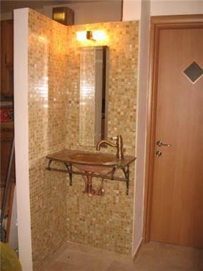 כיור לרחצת ידיים, כיור וברז בגוון נחושת, חיפוי קירות פסיפס, מיקום בכניסה לשירותים.