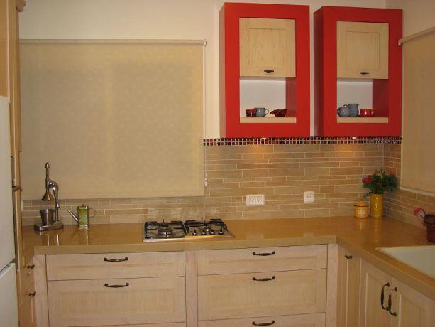 מטבח כפרי עם נגיעות מודרניות, עיצוב מטבח ארונות לבנים, חיפוי קירות באבן, שילוב צבע אדום,