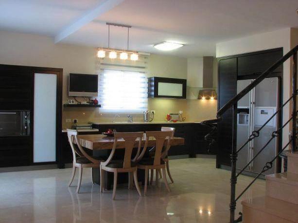 מטבח מרווח, סגנון קלאסי, פינת אוכל ממוקמת במרכז המטבח, כסאות מעוצבים, חלל גדול ומעוצב.