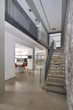 חלל כניסה מדרגות, מדרגות עץ מרחפות, מעקה ברזל בשילוב זכוכית, קיר לבנים,
