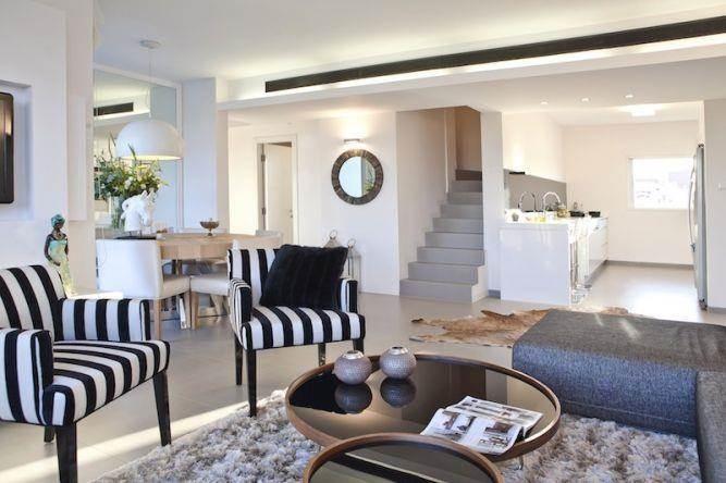 מבט אל הסלון, המטבח ופינת האוכל המעוצבים בסגנון מודרני. דופלקס בכפר סבא של אורית כוכבי