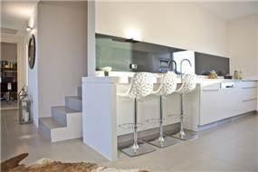 """מטבח מודרני המשלב כסאות בר גבוהים בפינת ישיבה. דופלקס בכפ""""ס בעיצוב אורית כוכבי"""